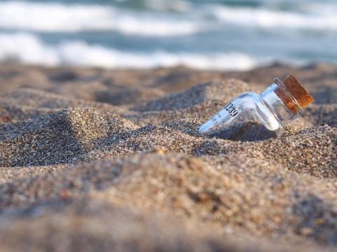 海、砂浜にうちげられた瓶